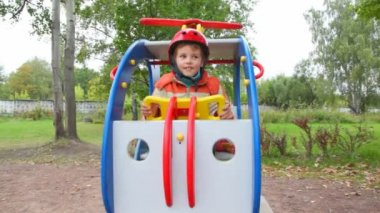 Ung pojke i hjälm svängningar i leksak helikopter i lekplats — Stockvideo