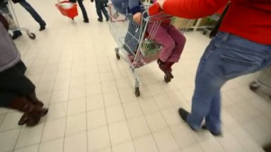 Woman going in mall with kids on shopping trolley — Stock Video