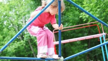 Little girl blonde in pink clothes climbs on iron rod on children's playground — Stock Video
