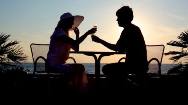 Silhouettes of man and woman drink brotherhood sits at table against sunset sky — Stock Video