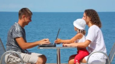 Smiling family of three persons with notebook sits at table, sea in background — Stock Video