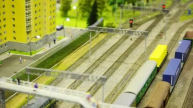 Toy train pushes tank wagon on rail in toy modern sity near multistorey apartment block — Stock Video
