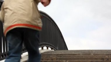 Boy runs upwards on steps of stone bridge with an iron handrail — Stock Video