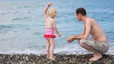 小石のビーチで海に小石を投げて彼は小さな娘を持つ男 — ストックビデオ