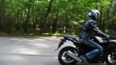 Two motorcyclists go on asphalt road. Moving camera — Stock Video