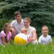 Family with ball sits in summer park — Stock Video