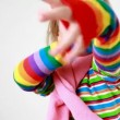 Girl in pink scarf and multicolor striped T-shirt wears gaudy gloves — Stock Video #26755617