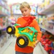 Boy examines toy excavator in store — Stock Video