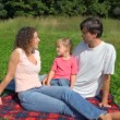 Happy family sits on field in summer park — Stock Video