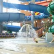 Two children come under fountain in indoor water park — Stock Video