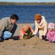 Family constructing sand buildings on beach — Stock Video #26756103
