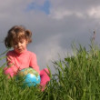 Girl with terrestrial globe sits on grass against sky — Stock Video