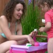 Young woman and little girl plays with toy tea service outdoor — Stock Video #26756267