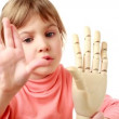 Girl waves hand and wooden model of human hand — Stock Video