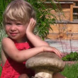 Portrait of cute little girl sits on green grass in outlet — Stock Video