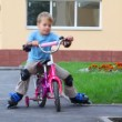 Boy in elstringed pads and knee-pads rollerblading with bicycle — Stock Video