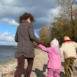 Family walking on sandy bank of river — Stock Video