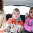 Mum, daughter and son sit on back seat of car — Stock Video #26756523
