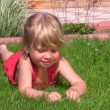 Portrait of cute little girl lying on green grass in outlet and dangles legs — Stock Video