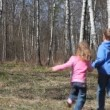 Boy with little sister runs from camera to spring forest, rotates her, runs back — Stock Video