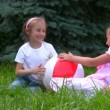 Girls sits with ball on grass in park and plays — Stock Video