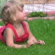 Stock Video: Portrait of cute little girl lying on green grass in outlet and dangles legs