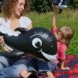 Woman and daughter plays with toy sharks in summer field — Stock Video