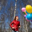 Happy smiling young woman holds bunch of balloons in spring forest — Stock Video