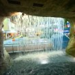 Stock Video: Through waterfall of stone cave seen bathing in pool in waterpark