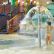 Stock Video: Womruns under fountain in pool in indoor water park