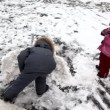 Boy and girl playing with snow and building a fortress — Stock Video #26757427