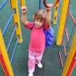 Girl on playground approaches to rings and hangs on them — Stock Video