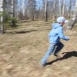 Happy little son runs to mother in spring forest, then hugs — Stock Video