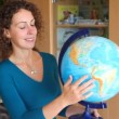 Woman rotates terrestrial globe in classroom — Stock Video