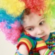 Girl in a ridiculous multicolor wig and gaudy striped T-shirt beats hands over her face — Stock Video