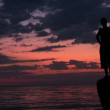 Silhouette of young man stands on rock against sunset — Stock Video