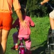 Parents helps a kids riding bicycles from camera in park — Stock Video #26758527