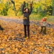 Woman and boy throwing leaves in park — Stock Video