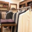 Rows of hangers with jacket and shelves with clothes and jeans — Stock Video