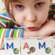 Video Stock: Girl in multicolor striped T-shirt has puted together cubes with letters for obtaining word Mama