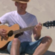 Man sits on beach and plays guitar — Stock Video