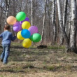 Stock Video: Boy with coloured balloons runs to spring forest from camera, then comes back