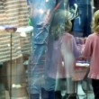 Stock Video: Little girl walking along museum display window