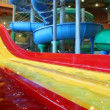 Stock Video: Large yellow plastic slide is filled water in large indoor waterpark
