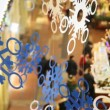 Close up paper snowflakes on cords, against shopping centre pavilions — Vidéo