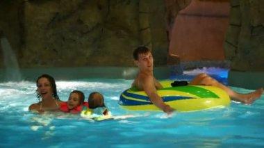 Frau, kinder und ein mann auf einem schlauchboot schwimmen im pool im wasserpark — Stockvideo