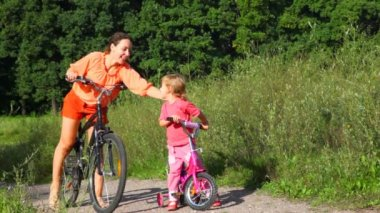 Mother pats on the back daughter, then both of them rides bicycles — Stock Video