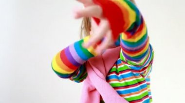Girl in a pink scarf and multicolor striped T-shirt wears gaudy gloves — Stock Video