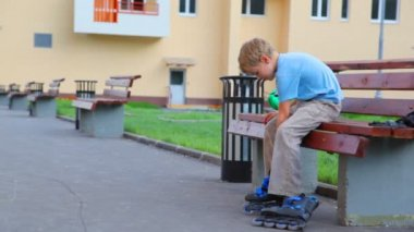 Boy sits on bench in foreyard and puts on roller skates — Stock Video