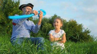 Uomo in pirata costume e la ragazza si siede sull'erba e rende la spada fuori dalla mongolfiera — Video Stock